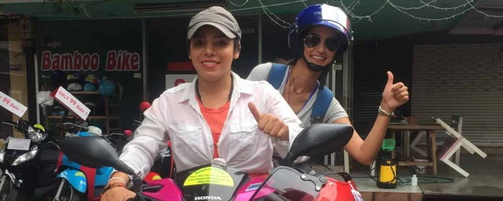 girls on a scooter giving thumbs up